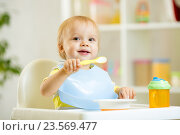 Купить «funny baby child boy eating itself with spoon in kitchen», фото № 23569477, снято 3 ноября 2014 г. (c) Оксана Кузьмина / Фотобанк Лори