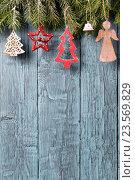 Купить «Винтажные рождественские украшения висят на деревянном фоне», фото № 23569829, снято 26 октября 2014 г. (c) Андрей Маслаков / Фотобанк Лори