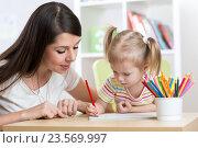 Купить «Young mother looking how her kid daughter drawing a picture», фото № 23569997, снято 2 февраля 2016 г. (c) Оксана Кузьмина / Фотобанк Лори