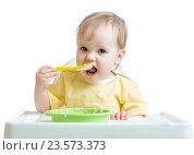 Купить «happy baby child sitting in chair with a spoon», фото № 23573373, снято 24 декабря 2014 г. (c) Оксана Кузьмина / Фотобанк Лори