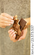 Купить «Женские руки держат кусочки шоколада», фото № 23573537, снято 8 сентября 2016 г. (c) Екатерина Тарасенкова / Фотобанк Лори
