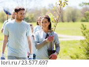 Купить «group of volunteers with trees and rake in park», фото № 23577697, снято 7 мая 2016 г. (c) Syda Productions / Фотобанк Лори