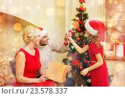 Купить «smiling family decorating christmas tree», фото № 23578337, снято 26 октября 2013 г. (c) Syda Productions / Фотобанк Лори