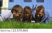 Купить «Трое студентов лежат на лужайке с телефонами», видеоролик № 23579865, снято 13 сентября 2016 г. (c) Виктор Аллин / Фотобанк Лори