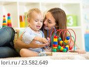 Купить «kid and mother play with educational toy», фото № 23582649, снято 6 октября 2014 г. (c) Оксана Кузьмина / Фотобанк Лори