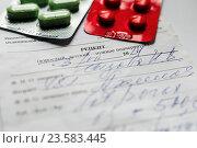Купить «Упаковки с таблетками лежат на медицинском рецепте выписанным врачом», эксклюзивное фото № 23583445, снято 23 сентября 2016 г. (c) Игорь Низов / Фотобанк Лори