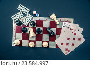 Купить «Various board games and figurines over checkers board», фото № 23584997, снято 16 августа 2015 г. (c) Роман Гадицкий / Фотобанк Лори
