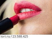 Beautiful woman applying red lipstick on lips against black background. Стоковое фото, агентство Wavebreak Media / Фотобанк Лори