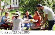 Купить «friends having barbecue party at summer garden», видеоролик № 23620905, снято 5 сентября 2016 г. (c) Syda Productions / Фотобанк Лори