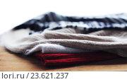 Купить «knitwear or woolen clothes on wooden table at home», видеоролик № 23621237, снято 19 сентября 2016 г. (c) Syda Productions / Фотобанк Лори