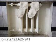 Белая батарея центрального отопления с шерстяными носками. Стоковое фото, фотограф Малахов Алексей / Фотобанк Лори
