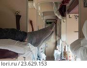 Купить «Ноги, торчащие в проход с верхней полки плацкартного вагона», эксклюзивное фото № 23629153, снято 16 июня 2016 г. (c) Вячеслав Палес / Фотобанк Лори