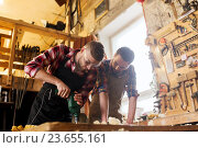 Купить «carpenters with drill drilling plank at workshop», фото № 23655161, снято 14 мая 2016 г. (c) Syda Productions / Фотобанк Лори