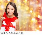 Купить «smiling woman in red dress with christmas gift», фото № 23655445, снято 22 сентября 2013 г. (c) Syda Productions / Фотобанк Лори