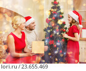 Купить «smiling family decorating christmas tree», фото № 23655469, снято 26 октября 2013 г. (c) Syda Productions / Фотобанк Лори