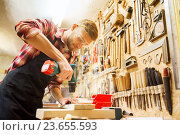 carpenter with drill drilling plank at workshop. Стоковое фото, фотограф Syda Productions / Фотобанк Лори