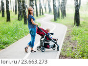 Купить «Красивая девушка с прогулочной коляской гуляет в парке», эксклюзивное фото № 23663273, снято 25 июля 2016 г. (c) Игорь Низов / Фотобанк Лори