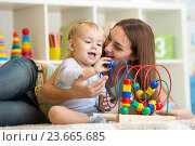 Купить «kid and mother play with educational toy indoor», фото № 23665685, снято 6 октября 2014 г. (c) Оксана Кузьмина / Фотобанк Лори