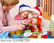 Купить «mother with daughters preparing for Christmas», фото № 23698793, снято 26 марта 2019 г. (c) Яков Филимонов / Фотобанк Лори