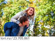 Купить «Young couple hugging and flirting in park.», фото № 23705861, снято 7 октября 2015 г. (c) Gennadiy Poznyakov / Фотобанк Лори