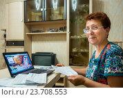 Купить «Пожилая улыбающаяся женщина использует в систему онлайн банка для оплаты счетов», эксклюзивное фото № 23708553, снято 19 июня 2016 г. (c) Вячеслав Палес / Фотобанк Лори
