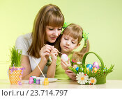 Купить «mother and child girl paint easter eggs over green background», фото № 23714797, снято 20 февраля 2013 г. (c) Оксана Кузьмина / Фотобанк Лори