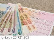Купить «Деньги лежат на бланке ОСАГО», эксклюзивное фото № 23721805, снято 7 октября 2016 г. (c) Яна Королёва / Фотобанк Лори