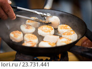 Купить «close up of scallops frying in cast iron pan», фото № 23731441, снято 11 июня 2016 г. (c) Syda Productions / Фотобанк Лори