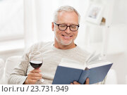 Купить «happy senior man drinking wine and reading book», фото № 23731949, снято 7 июля 2016 г. (c) Syda Productions / Фотобанк Лори