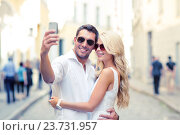 Купить «smiling couple with smartphone in the city», фото № 23731957, снято 14 июля 2013 г. (c) Syda Productions / Фотобанк Лори