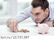 Купить «businessman with piggy bank and coins at office», фото № 23731997, снято 18 июня 2015 г. (c) Syda Productions / Фотобанк Лори