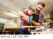 Купить «father and son with drill working at workshop», фото № 23732185, снято 14 мая 2016 г. (c) Syda Productions / Фотобанк Лори