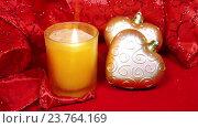 Купить «Новогодние украшения и горящая свеча на красном фоне», видеоролик № 23764169, снято 12 октября 2009 г. (c) Куликов Константин / Фотобанк Лори