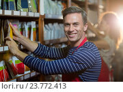 Купить «Portrait of male staff arranging grocery items on shelf», фото № 23772413, снято 17 мая 2016 г. (c) Wavebreak Media / Фотобанк Лори