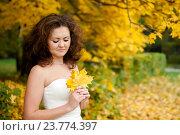 Купить «Невеста на прогулке в осеннем лесу с кленовым листьями в руках», эксклюзивное фото № 23774397, снято 4 октября 2016 г. (c) Игорь Низов / Фотобанк Лори