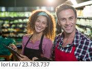 Купить «Smiling staffs writing on clipboard in organic section», фото № 23783737, снято 17 мая 2016 г. (c) Wavebreak Media / Фотобанк Лори