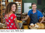 Купить «Smiling woman standing at bakery counter», фото № 23789521, снято 17 мая 2016 г. (c) Wavebreak Media / Фотобанк Лори