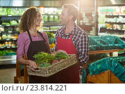 Купить «Smiling staffs holding basket of vegetable in organic section», фото № 23814221, снято 17 мая 2016 г. (c) Wavebreak Media / Фотобанк Лори