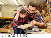 Купить «father and little son with wood plank at workshop», фото № 23818085, снято 14 мая 2016 г. (c) Syda Productions / Фотобанк Лори
