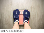 Купить «Девушка стоит на напольных весах в новогодних носках», фото № 23840361, снято 18 октября 2016 г. (c) Анна Рахимова / Фотобанк Лори