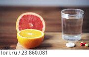 Купить «orange, grapefruit and glass of water with pills», видеоролик № 23860081, снято 18 октября 2016 г. (c) Syda Productions / Фотобанк Лори