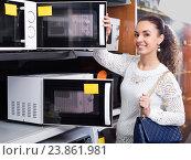Купить «Woman choosing new microwave», фото № 23861981, снято 22 августа 2018 г. (c) Яков Филимонов / Фотобанк Лори
