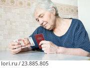 Пожилая женщина с пенсионным удостоверением и пятью тысячами рублей. Единовременная выплата пенсионерам. Стоковое фото, фотограф Дудакова / Фотобанк Лори