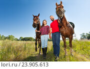 Купить «Young couple holding hands and walking with horses», фото № 23905613, снято 3 июля 2016 г. (c) Сергей Новиков / Фотобанк Лори