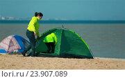 Семья заходит в зеленую палатку на пляже. Стоковое видео, видеограф Tatiana Kravchenko / Фотобанк Лори