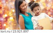 Купить «happy mother and girl with gift box over lights», фото № 23921897, снято 25 августа 2013 г. (c) Syda Productions / Фотобанк Лори