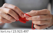 Купить «woman knitting with needles and red yarn», видеоролик № 23923497, снято 22 октября 2016 г. (c) Syda Productions / Фотобанк Лори