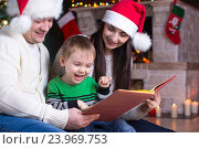 Купить «Family on Christmas Eve by the fireplace reading a book to their child», фото № 23969753, снято 16 января 2016 г. (c) Оксана Кузьмина / Фотобанк Лори