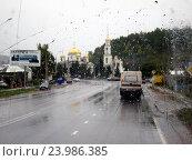 Купить «Вид на дорогу во время дождя через мокрое стекло автомобиля (фокус на стекле)», фото № 23986385, снято 21 сентября 2013 г. (c) Светлана Кириллова / Фотобанк Лори