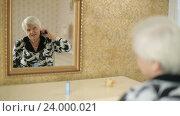 Купить «Старая женщина расчесывает седые волосы», видеоролик № 24000021, снято 28 октября 2016 г. (c) Илья Шаматура / Фотобанк Лори